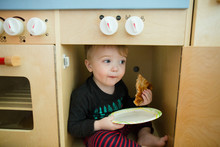 Toddler Boy Smiles While Eating Pizza Sitting Inside Of Play Kitchen