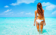 Leinwanddruck Bild - Travel vacation wallpaper - Beautiful young pretty blonde girl in white bikini with white sand on her perfect sport sexy body relax in sea of white sand paradise tropical Maldives beach at sunny day
