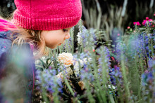 Young Toddler Girl Smelling Flowers At A Garden Center