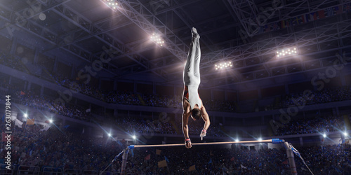 Male athlete doing a complicated exciting trick on horizontal gymnastics bars in a professional gym Canvas Print