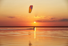 Kiteboarding On A Lake At Sunset With A Sun Path