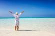canvas print picture - Mann in weißer Sommerkleidung steht am tropisch Strand und genießt die Freiheit