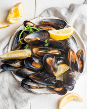 Plate With Boiled Mussels In Armor With Lemon Pieces
