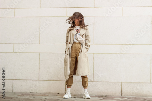 fototapeta na lodówkę Portrait shooting of a stylish girl. Beige shades. Trends of spring and summer 2019. Pants of cork.Trench cloak, a wide jacket.