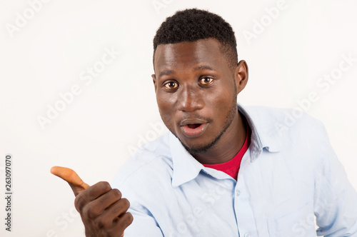 Fotografering  Portrait of surprised young man with hand gesture