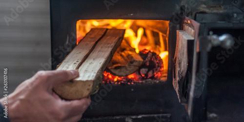 Fotografiet Man putting log to wood burning stove