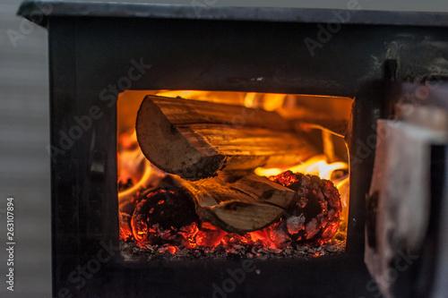 Wood stove with fire burning inside Fototapeta