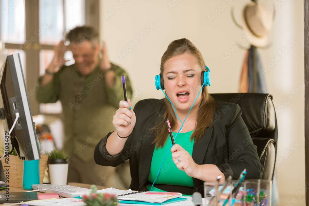 Fototapeta Woman with Headphones Singing Loudly and Annoying Colleague