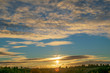 beautiful sunset above the village. scenic countryside landscape. clouds and sun in the sky