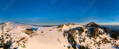 Foto  Dochia chalet and Toaca peak at sunrise in Ceahlău Mountains National in winter