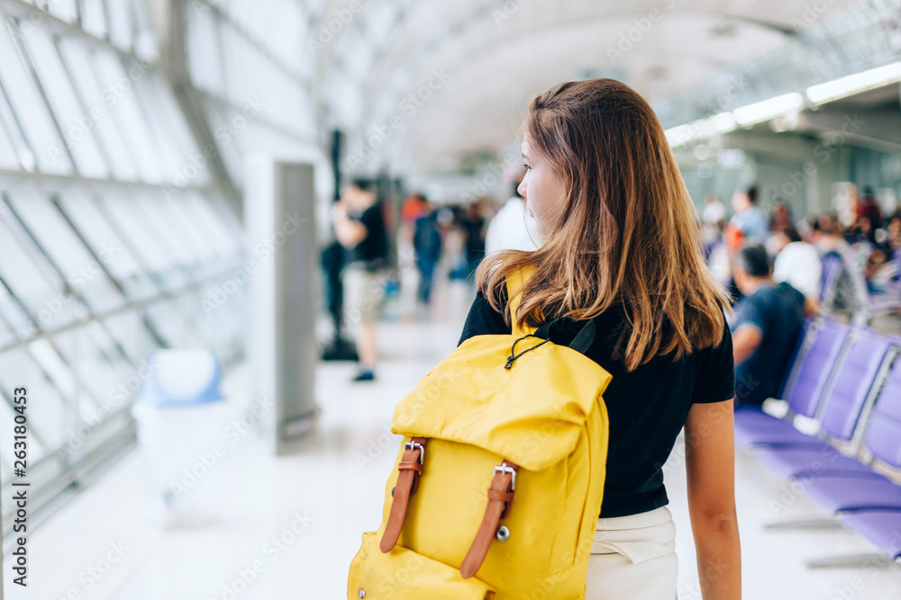 Fototapeta Teen girl waiting for international flight in airport departure terminal