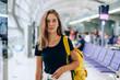 Leinwandbild Motiv Teen girl waiting for international flight in airport departure terminal