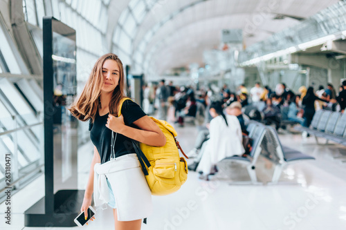 Photo Teen girl waiting for international flight in airport departure terminal