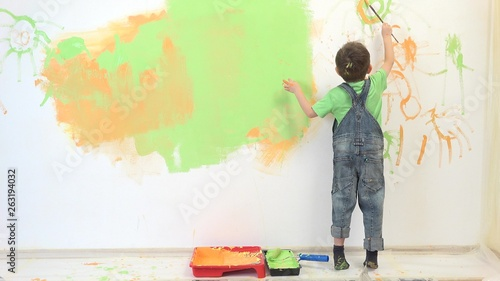 Little artist painting white wall, amusing child have fun Canvas Print