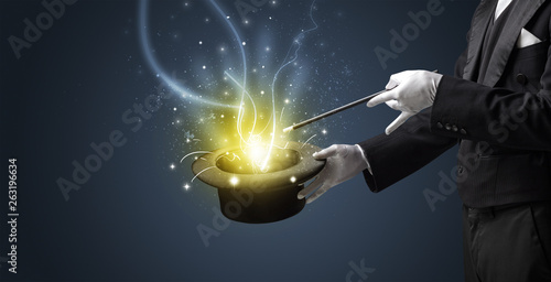Magician hand conjure with wand  light from a black cylinder Fototapete