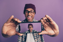 Closeup Photo Portrait Of Cheerful Excited Laughing Screaming Fooling Millenial Influencer Holding Smart Phone In Hands Making Taking Selfie On Instagram Isolated Violet Background