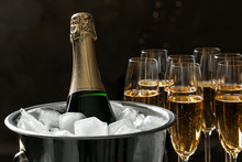 Bottle In Bucket With Ice Near Glasses Of Champagne On Dark Background