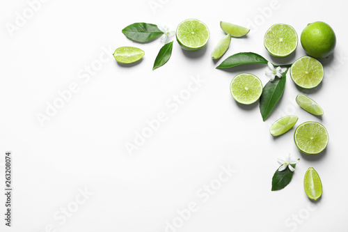 Fotografie, Obraz  Frame made of limes, flowers and leaves on white background, top view with space for text