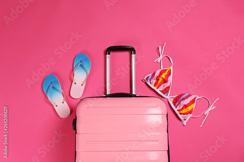 Stylish suitcase, bikini top and flip flops on color background, top view - 263208629