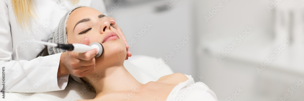 Fototapeta Beautiful woman in professional beauty salon during photo rejuvenation procedure