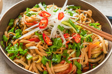 Asian Vegan Lunch - Spicy Chow Mein Noodles With Carrots, Pepper And Spinach With Sliced Radish, Spring Onions And Chili Peppers On A Plate