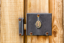 A Weathered And Worn Metal Lock Mechanism With Rusted Screws On A Wooden Gate And Fence Post Close Up