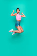 Vertical full length side profile body size photo beautiful she her funny yelling trendy hairdo jump high lucky lottery wear casual pink tank-top jeans denim shorts isolated teal turquoise background