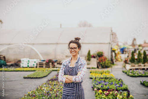 Charming Caucasian florist standing outdoors with arms crossed Canvas Print