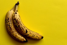 Two Ripe Bananas With Brown Spots On The Bright Yellow Table, Top View, Empty Space.