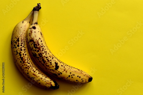 Valokuva  Two ripe bananas with brown spots on the bright yellow table, top view, empty space