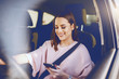 Leinwandbild Motiv Attractive young Caucasian brunette with toothy smile and dressed elegant driving car and looking at smart phone.