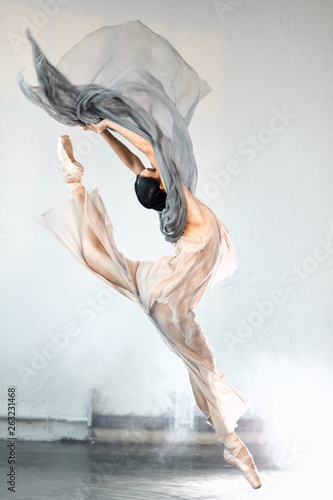 Carta da parati Adorable dar-haired female dancer performing on scene her part of concert jumping high in the air expressing emotions and beauty of classical ballet
