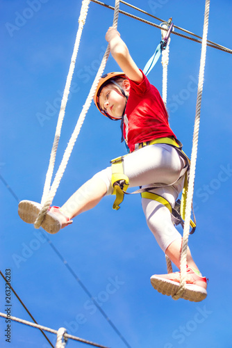 Little brave caucasian girl at outdoor treetop climbing adventure park Canvas Print