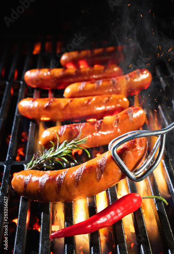 Fototapeta Delicious sausages sizzling over the coals on barbecue grill obraz
