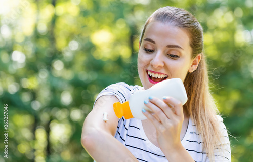 Fototapeta Young woman with sunscreen on a bright summer day in the forest obraz