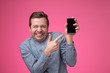 canvas print picture - Funny young european man pointing to phone screen of his smartphone
