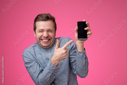 Foto  Funny young european man pointing to phone screen of his smartphone