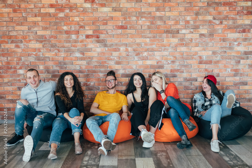 Fototapety, obrazy: Millennials chilling out in leisure zone after successful hard working day. Young people sitting in cushion chair, laughing.
