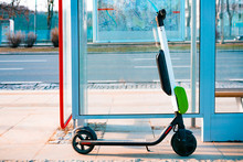 Electric Scooter Stands Near Public Bus Stop. Electric Scooters Stand Along The Streets Of Downtown. The Public Scooters Are Available To Rent As A Means Of Transportation Throughout The City