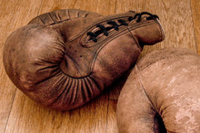 Boxing Gloves. Old Vintage Retro Pair Of Leather Worn Mittens Are On The Wood Table. Red Colors And Soft Lights. Gloves Of Retired Boxer And Fighter