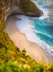FototapetaView of a people couple on the beach on Bali, Indonesia. Vacation and adventure. Beach and turquoise water. Top view from drone at beach, azure sea and relax couple. Travel and relax - image