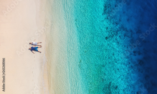 Deurstickers Ontspanning Aerial view of a people couple on the beach on Bali, Indonesia. Vacation and adventure. Beach and turquoise water. Top view from drone at beach, azure sea and relax couple. Travel and relax - image