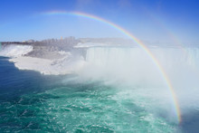 Rainbow Over The Horseshoe Falls Over Frozen Ice And Snow On The Niagara River In Niagara Falls In March 2019