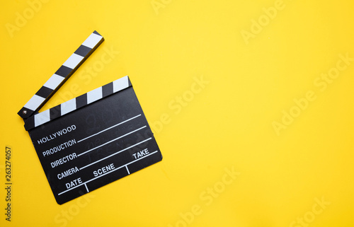 Stampa su Tela Movie clapperboard on yellow color background, top view