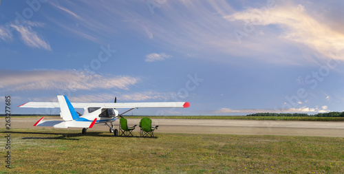Rear side view of light aircraft with piston engine on airfield with two folding Wallpaper Mural