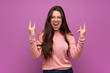 Teenager girl over purple wall making rock gesture