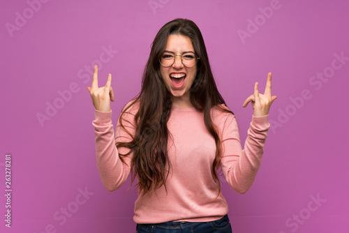 Teenager girl over purple wall making rock gesture Fototapete