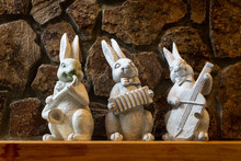 Three Ceramic, White Bunnies Playing Musical Instruments On The Fireplace Mantle.