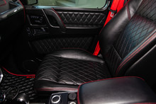 The Interior Of The Car Mercedes Benz G-class G350 With A View Of The Steering Wheel, Dashboard, Seats And Multimedia System With Black Leather And Red Thead Rombus Trim
