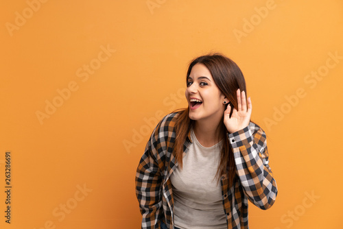 Foto  Young woman over brown wall listening to something by putting hand on the ear